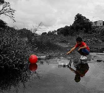 Bambino che gioca con la palla vicino ad acqua inquinata